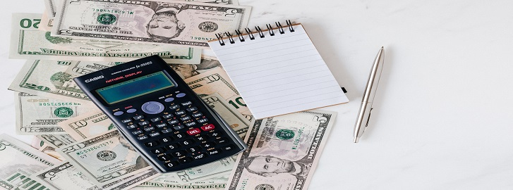 Calculator and note pad lying on money